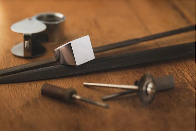 Anel de prata com sinete vazio e ferramentas de joalheiro em tamplate de mesa de madeira antiga para maquete de gravador