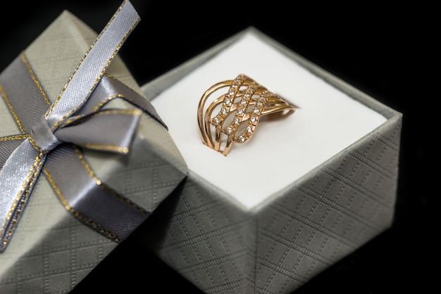 Anel dourado com diamante na caixa isolada no preto