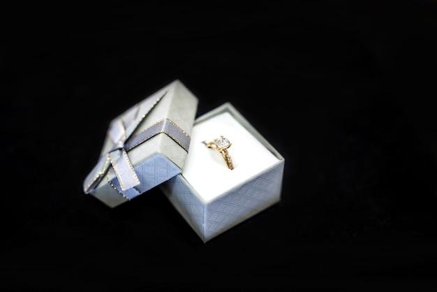 Anel dourado em caixa de presente prateada em fundo preto