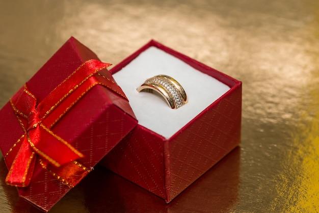 Anel dourado em caixa de presente vermelha em fundo dourado
