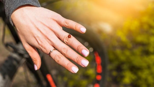 Anel e joaninha em uma mão de mulher