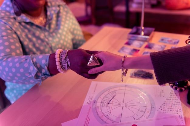 Anel enorme. cartomante afro-americano com um enorme anel apertando a mão de uma mulher