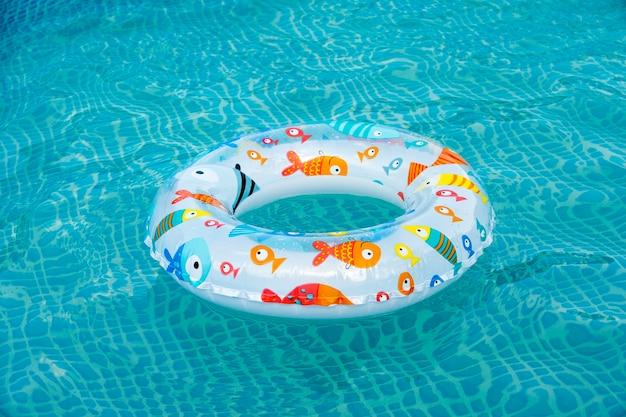 Anel flutuante na piscina de água azul com ondas refletindo no sol de verão