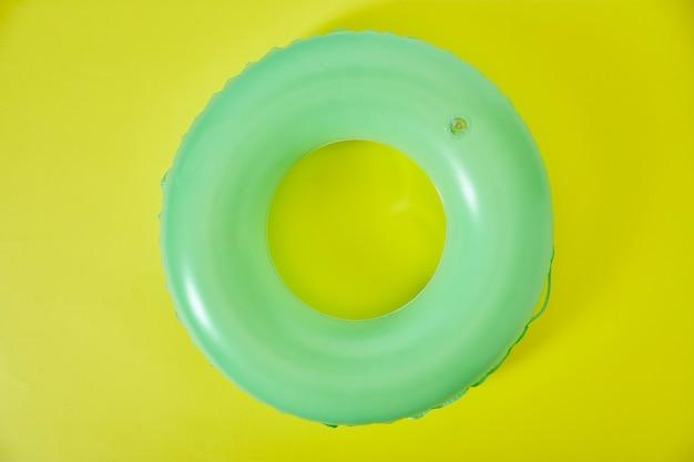 Anel inflável verde sobre fundo amarelo
