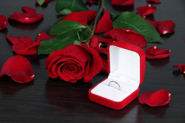 Anel rodeado por rosas e pétalas em close-up de mesa de madeira