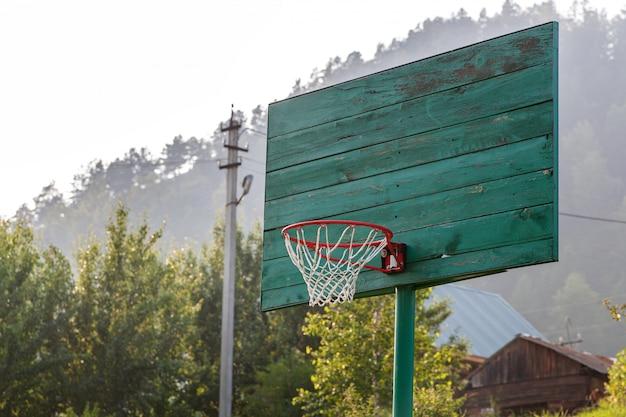 Anel velho de basquete verde com uma rede para jogar basquete
