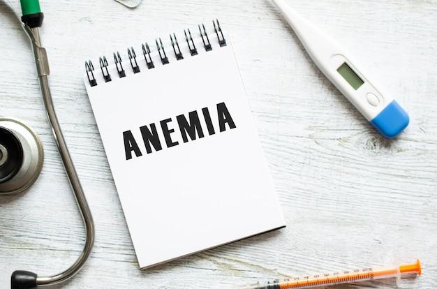 Anemia é escrita em um caderno sobre uma mesa de madeira clara ao lado de um estetoscópio