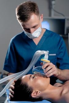 Anestesiologista fazendo anestesia de ingalação para o paciente. o médico coloca uma máscara no paciente antes de iniciar a operação