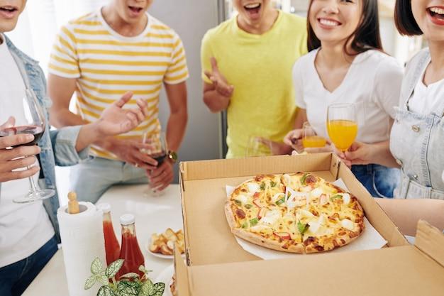Anfitriã da festa abrindo caixa de pizza