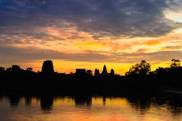 Angkor wat céu dramático na reflexão de silhueta de fachada principal de amanhecer na lagoa de água