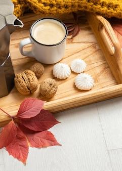 Ângulo alto da bandeja com folha e xícara de café