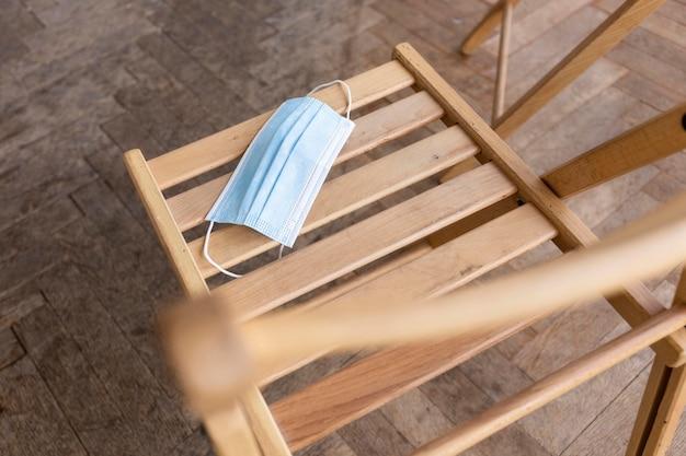 Ângulo alto da cadeira vazia com máscara médica preparada para sessão de terapia de grupo