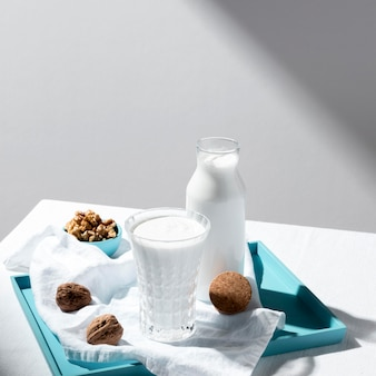 Ângulo alto da garrafa de leite e copo com nozes