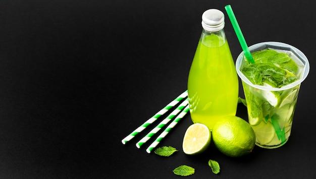 Ângulo alto da garrafa e copo com refrigerante e hortelã