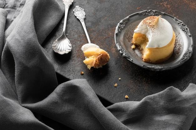 Ângulo alto da sobremesa com colheres e pano