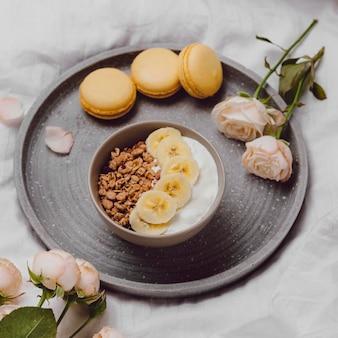 Ângulo alto da tigela de café da manhã com cereais e macarons