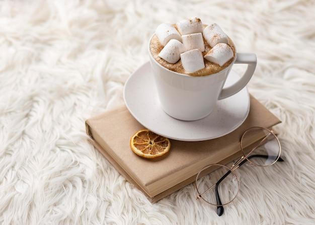 Ângulo alto da xícara com marshmallows no livro com copos e frutas cítricas secas