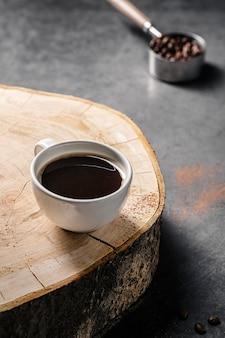 Ângulo alto da xícara de café na placa de madeira