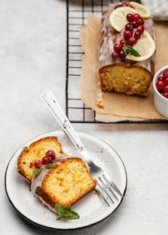 Ângulo alto das fatias de bolo no prato com frutas e garfo