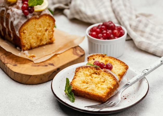 Ângulo alto das fatias de bolo no prato com frutas vermelhas