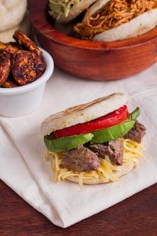 Ângulo alto de arepa com tomate e carne