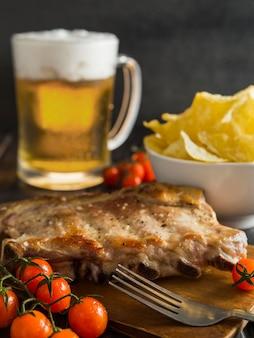 Ângulo alto de bife com cerveja e batatas fritas
