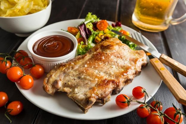 Ângulo alto de bife no prato com cerveja e salada