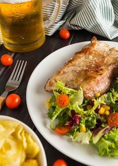 Ângulo alto de bife no prato com salada e copo de cerveja