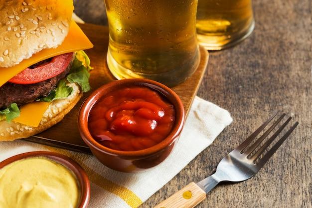 Ângulo alto de copos de cerveja com cheeseburger e molho