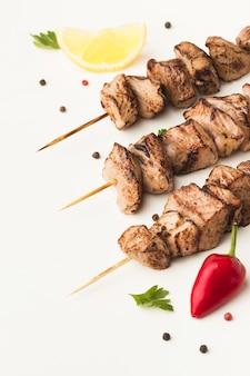 Ângulo alto de delicioso kebab com pimenta e limão