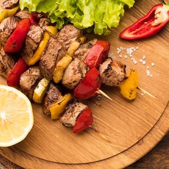 Ângulo alto de delicioso kebab na tábua de cortar com limão e salada