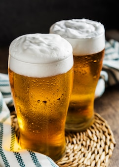 Ângulo alto de dois copos de cerveja com pano