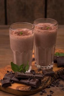 Ângulo alto de dois copos de milkshake com chocolate e menta