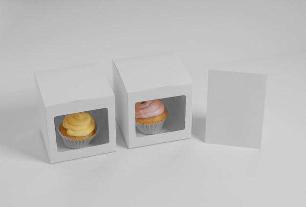 Ângulo alto de dois cupcakes com caixas de embalagem e cartão em branco