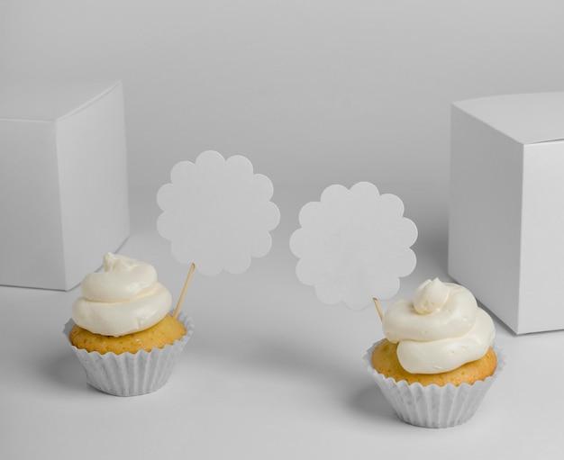 Ângulo alto de dois cupcakes com caixas de embalagem