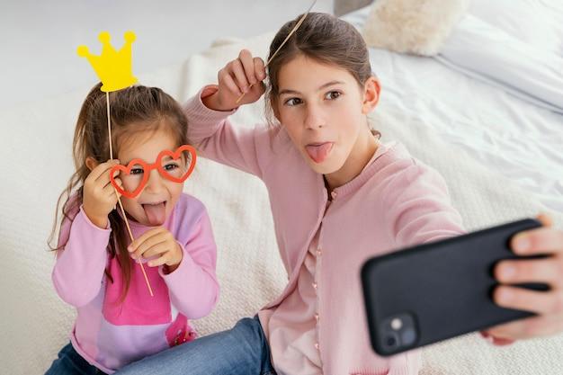 Ângulo alto de duas irmãs em casa tirando uma selfie