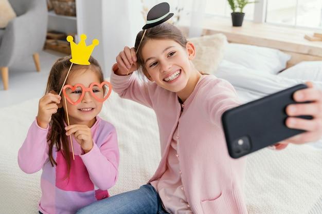 Ângulo alto de duas irmãs sorridentes em casa tirando uma selfie