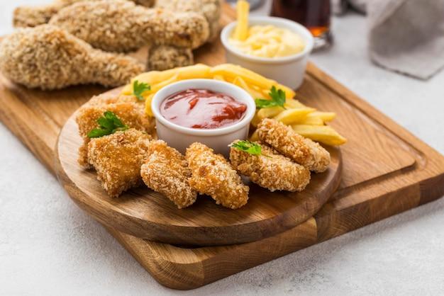 Ângulo alto de pernas de frango frito e nuggets com molho