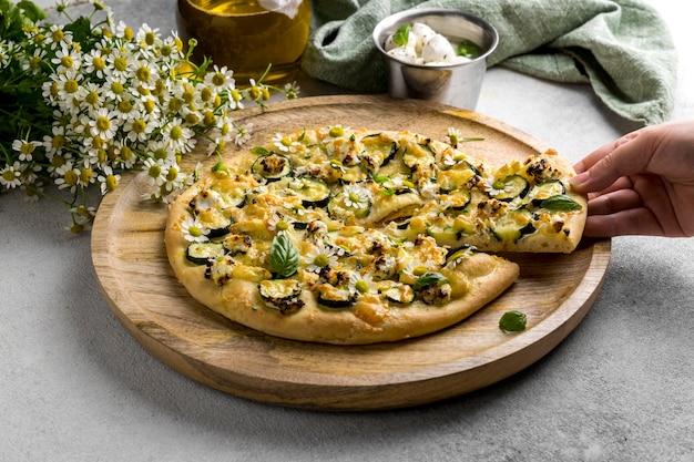 Ângulo alto de pizza com flores de camomila