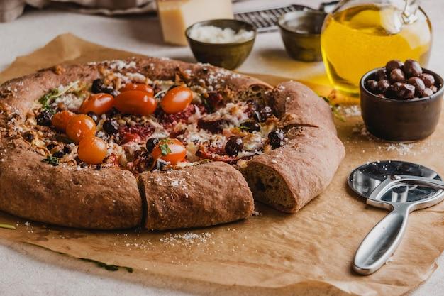Ângulo alto de pizza deliciosa com cortador de pizza e tomates
