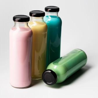 Ângulo alto de quatro garrafas de suco multicoloridas