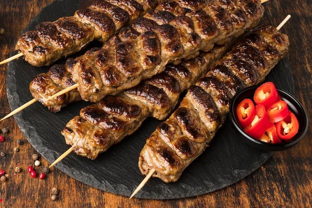 Ângulo alto de saboroso kebab com carne na ardósia