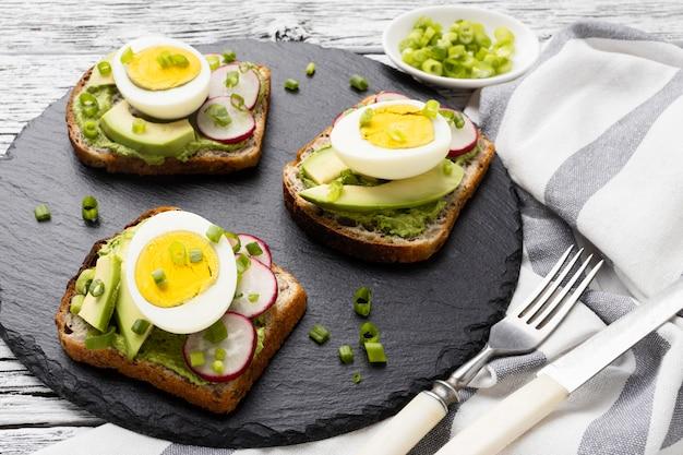 Ângulo alto de sanduíches com ovo e abacate