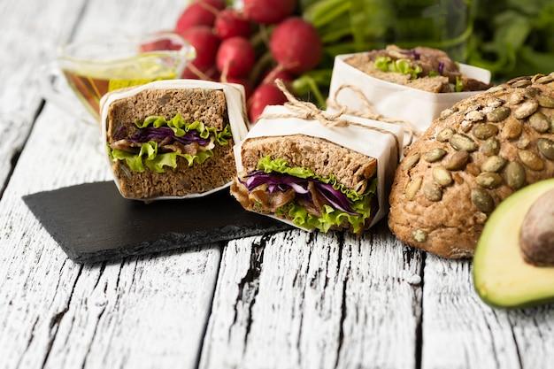 Ângulo alto de sanduíches em ardósia com abacate