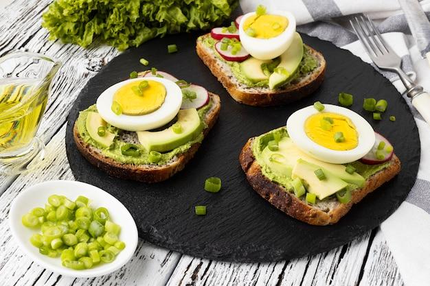 Ângulo alto de sanduíches em ardósia com ovo e abacate