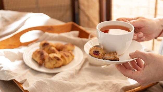 Ângulo alto de sobremesas na bandeja com a pessoa segurando uma xícara de chá