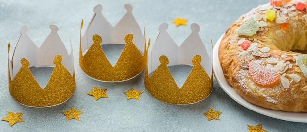 Ângulo alto de três coroas com sobremesa para o dia da epifania