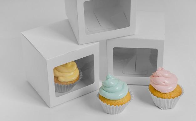 Ângulo alto de três cupcakes com caixas de embalagem