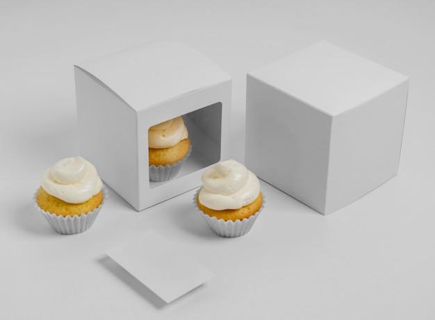 Ângulo alto de três cupcakes com duas caixas de embalagem e cartão em branco