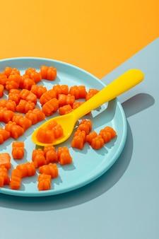 Ângulo alto de ursinhos de goma no prato com colher